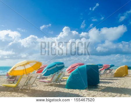 Colorful Beach umbrellas/parasols and cabanas at empty morning Miami beach