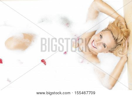 Caucasian Sensual Blond Woman Resting in Foamy Bathtub With Flowery Petals Added. Horizontal Shot