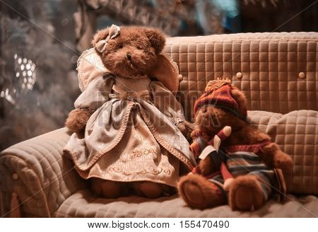 Plush toys teddy bear in dress and her friend sitting on the sofa near Christmas tree
