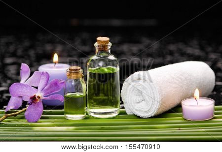 tranquil spa scene- purple orchid with candle ,oil green plant, towel