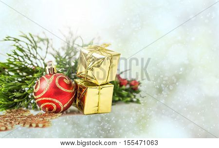 Christmas decoration - red ballgolden gift box against beautiful bokeh like snow