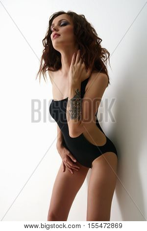 Erotica. Photo of sensual brunette posing in black bodysuit