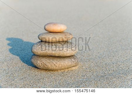 Cairn on the gray sand in the rays of sunset with shadow