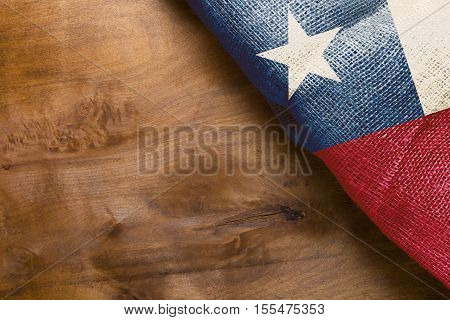 Flag of the State of Chile. Cloth tarpaulin on a wooden background.