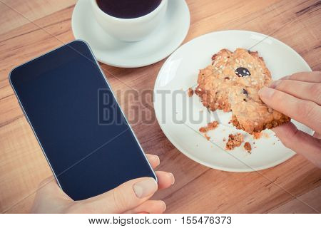 Vintage Photo, Hand Of Woman Using Mobile Phone, Oatmeal Cookies And Cup Of Coffee