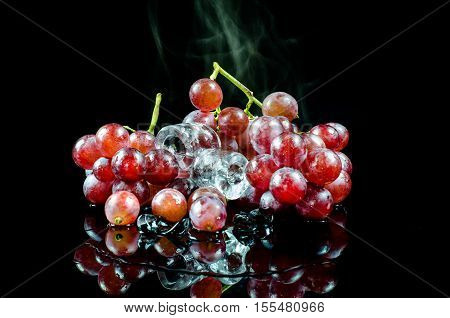 red grape on iceisolated on black background