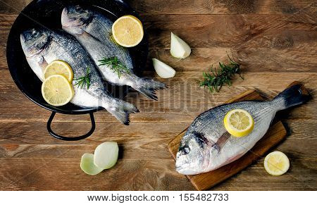 Fresh Fishes With Herbs On A Wooden Table.