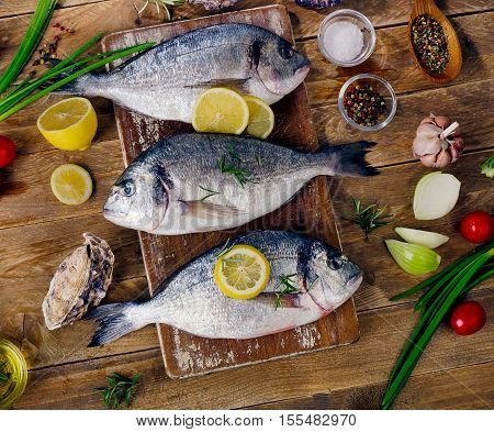 Fresh Fish With Herbs, Spices And Vegetables On  A Wooden Background.
