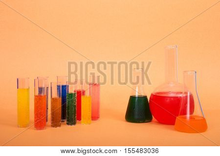 many vials and beakers full of bubbling colorful solutions for science experiment testing research. .Bright vibrant colors orange background. Copy space