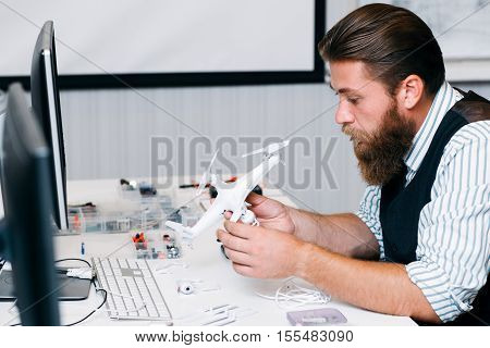 Electronic toy repair shop, . Bearded master disassembling broken hexacopter for renovation. Business, occupation, technology concept