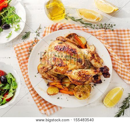 Whole Roasted Chicken With Vegetables And Salad On A Wooden Background.