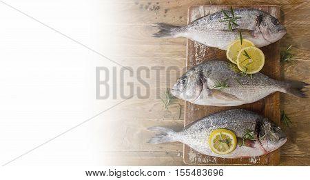 Fresh Fish With Lemon On  Wooden Background.