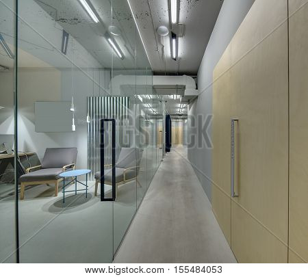 Luminous corridor in the office in a loft style. On the left there are rooms with glass walls and doors. On the right there is a room with a wooden wall and door. There are armchairs and tables.