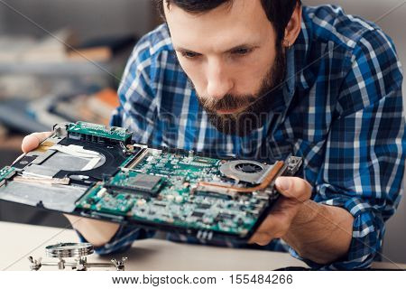Engineer studying computer motherboard, close-up. Bearded repairman examing electronic circuit to find failure issue. Repair shop, technology, occupation concept