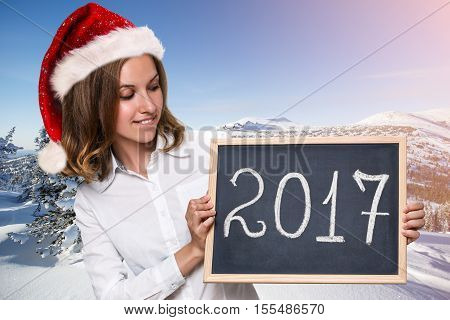 Cute girl in santa red hat with new year date on chalkboard in snowy landscape