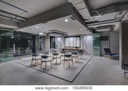 Business interior in a loft style with brick walls, concrete columns and a  presentation zone. Zone has many gray chairs, a long wooden table with a laptop, a screen and a projector. Horizontal.