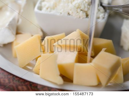 Cheese slices on plate close up with copy space.