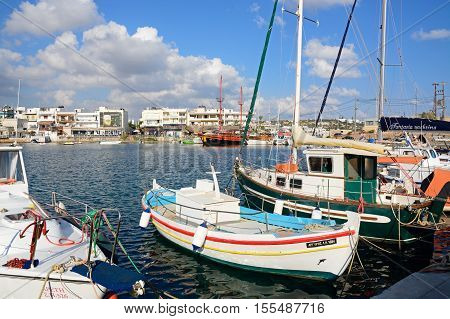HERSONISSOS, CRETE - SEPTEMBER 14, 2016 - Traditional fishing boats in the harbour with waterfront restaurants to the rear Hersonissos Crete Europe, September 14, 2016.