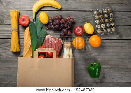 Paper bag full of different groceries on wooden table close up top view