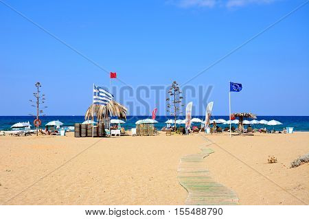 MALIA, CRETE - SEPTEMBER 14, 2016 -View of Potamos beach with flags and parasols and the sea to the rear Malia Crete Greece Europe, September 14, 2016.
