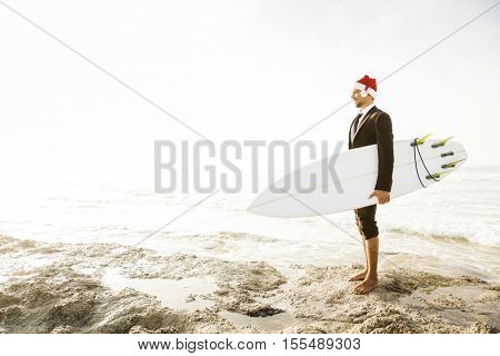 Business surfist wearing a Santa hat and holding a surfboard