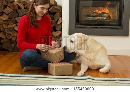 Beautiful woman at home wrapping presents for Christmas in the company of her dog