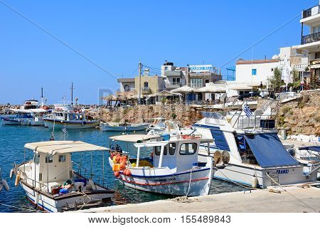 SISSI, CRETE - SEPTEMBER 14, 2016 - Boats moored in the harbour with waterfront restaurants to the rear Sissi Crete Europe, September 14, 2016.