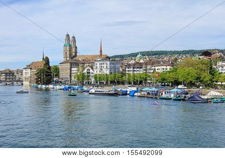 Zurich, Switzerland - 25 May, 2016: the Limmat river, people in boats and on the Limmatquai quay, historic buildings and towers of the Grossmunster Cathedral in the background. Zurich is the largest city in Switzerland.
