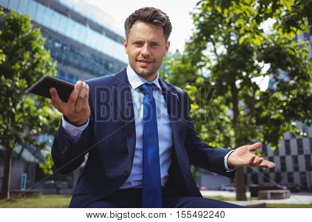 Portrait of handsome businessman holding mobile phone outside office