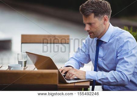 Handsome businessman using laptop at outdoor café