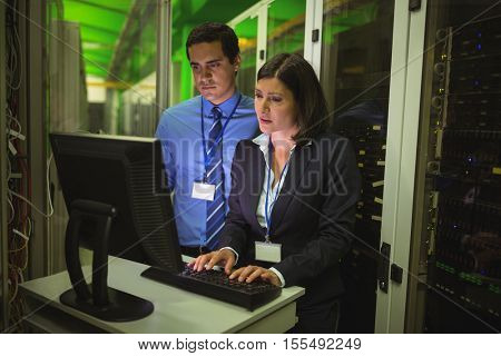 Technicians working on personal computer while analyzing server in server room