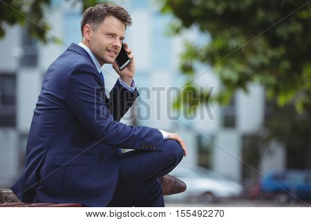 Handsome businessman talking on mobile phone outside office