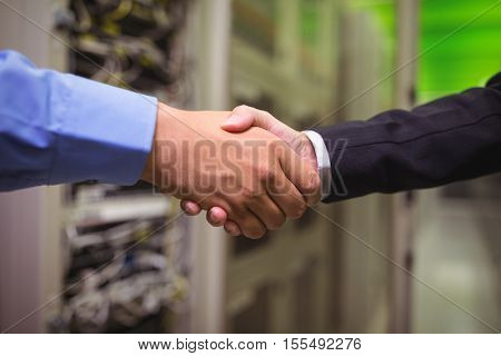 Close-up of technicians shaking hands in server room