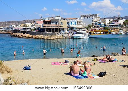 SISSI, CRETE - SEPTEMBER 14, 2016 - Tourists in the sea and on the beach with views of the harbour and town Sissi Crete Greece Europe, September 14, 2016.