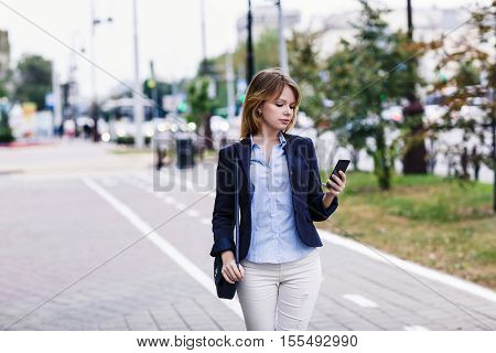 Young woman walking and using smart phone on the street.
