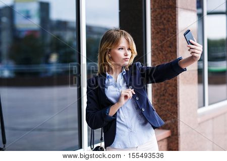 Young woman making selfie photo outside an office building