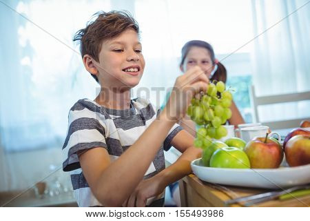 Portrait of smiling boy holding a bunch of grapes at breakfast table