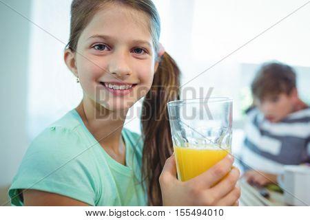 Smiling girl having orange juice at home