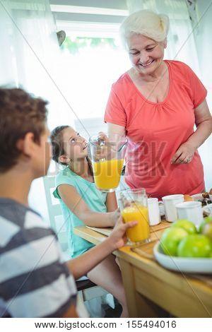 Grandmother pouring orange juice in glass for her grandchildren