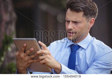 Businessman using digital tablet at outdoor cafe