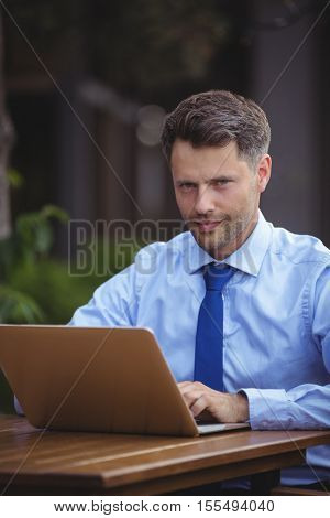 Portrait of handsome businessman using laptop at outdoor cafe