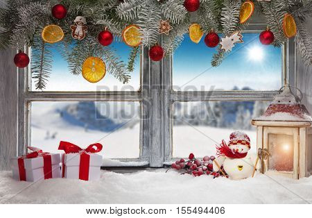 Vintage wooden window overlook winter landscape. Christmas decoration on foreground