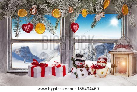 Vintage wooden window overlook winter landscape. Christmas decoration on foreground