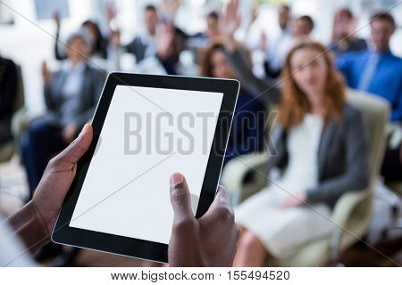 Close-up of businessperson using digital tablet during meeting in office