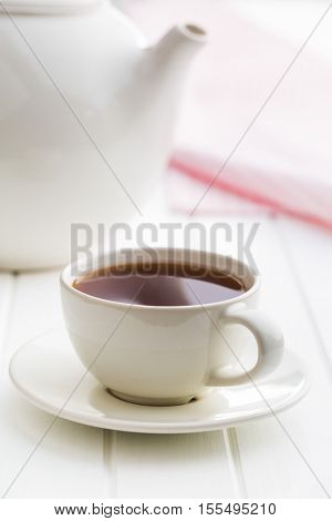 A cup of black tea and teapot on white table.