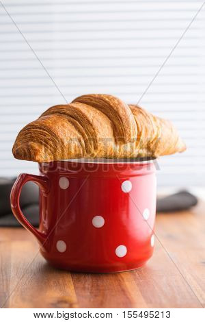 Tasty buttery croissant on red cup in kitchen on wooden table.
