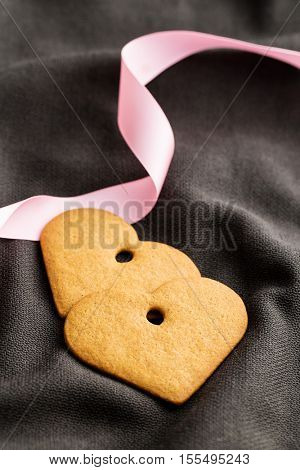 Two gingerbread hearts with pink ribbon on brown fabric.