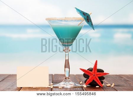Blank greeting card, cocktail, starfish and stones on a background of the sea.