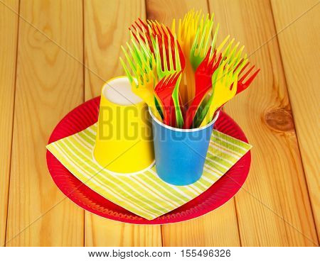 Bright disposable paper cups, plastic forks and a plate on a background of light wood.