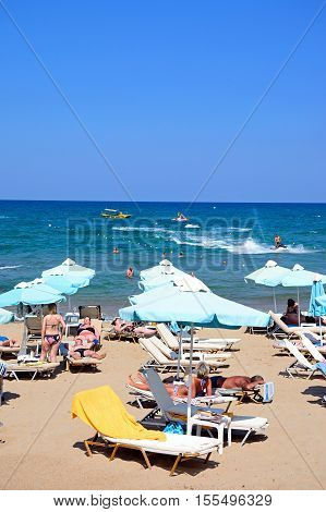STALIDA, CRETE - SEPTEMBER 14, 2016 - Tourists relaxing on the beach with views towards the sea Stalida Crete Europe, September 14, 2016.